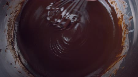 помадка : Close up hand mixing melted liquid dark chocolate using whisk. Confectionery Confectioner prepares dessert, sauce.
