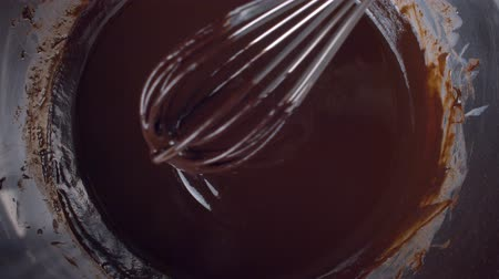 roztavený : Close up hand mixing melted liquid dark chocolate using whisk. Confectionery Confectioner prepares dessert, sauce.