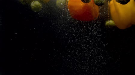 plash : Close up brussels sprouts and paprika falling into the water with a splash and bubbles on black background