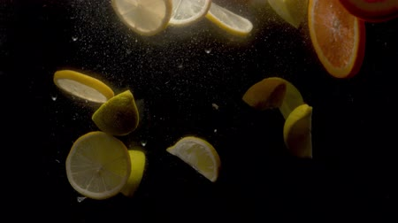 citrom és narancsfélék : Close up sliced fresh lemons and oranges falling into the water on black background Stock mozgókép