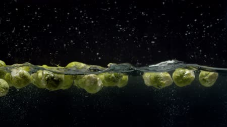 plash : Close up brussels sprouts falling into the water with a splash and bubbles on black background