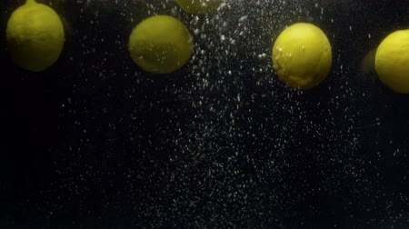 plash : Close up fresh lemons falling into the water with a splash on black background Stock Footage
