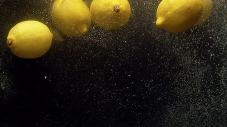 plash : Close up fresh lemons falling into the water with a splash and bubbles on black background