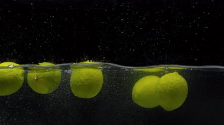 clear liquid : Close up fresh lemons falling into the water with a big splash on black background Stock Footage