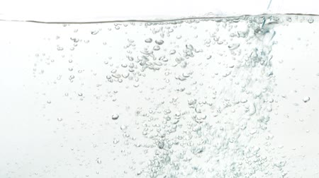 clear liquid : Water bubbles. A stream of water pouring into an aquarium on a white background. Close up flowing water in slow motion.