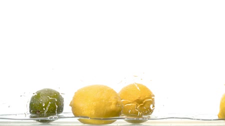 plash : Close up fresh lemons falling into the water on white background. Water drops on the glass and lemons. Slow motion Stock Footage