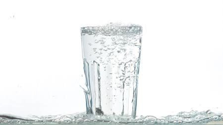 torrente : Water pouring into a glass on a white background. Close up flowing water in slow motion.