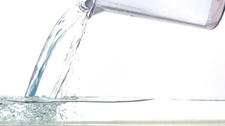 torrente : Close up water pouring from a jug into an aquarium on a white background. Flowing water in slow motion. Vídeos