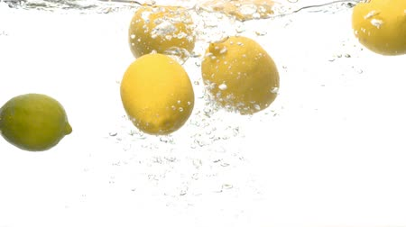 plash : Close up fresh lemons falling into the water with a big splash and bubbles on white background. Slow motion