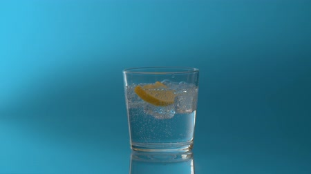 охлажденный : Close up mineral fizzy water pouring into a glass with ice and slice of lemon on a blue background