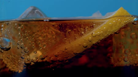 kola : Rising gas bubbles in a glass with cola extreme close up. Sliced lemon and pieces of ice floating on the coca surface on blue background. Soda carbonated drink into a drinking glass