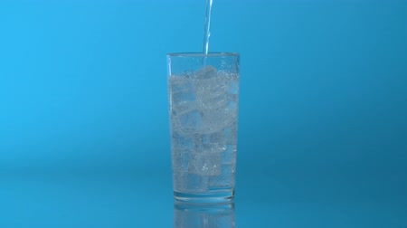 tonik : Close up mineral sparkling water pouring into a glass with ice on a blue background Stok Video