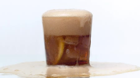 kabarcıklı : A cola is poured into a glass with ice cubes and sliced lemon. Foam rises in a glass. The bubbly drink overflows and spills onto the table. Close up, white background, slow motion