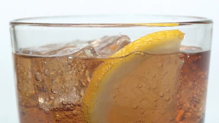 cola : Extreme close up of soda with rising gas bubbles. Sliced lemon and pieces of ice floating on the soda surface on white background. Soda carbonated drink into a drinking glass. Slow motion