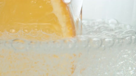 enchimento : Mineral fizzy water pouring into a glass with a slice of orange. Extreme close up naturally carbonated mineral water on white background. Slow motion Vídeos