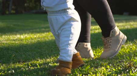 holding steady : Baby boy walking first steps outdoor in the grass with mother help. Low angle slow motion shot of toddler and mom on a sunny day.