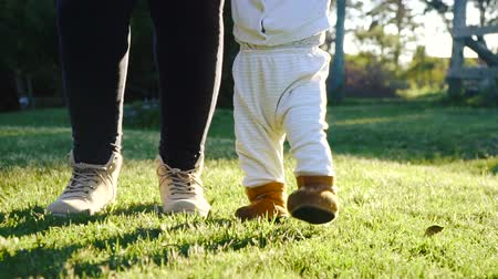 holding steady : My first steps: baby walking at the park with mother help in a sunny spring day. Low angle view of woman teaching newborn child to walk. Stock Footage