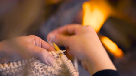 crochet : Close up of woman hands knitting by fireplace in warm winter scene. Over the shoulder camera view, girl doing handmade indoors season activity with wool at home, 4k. Stock Footage