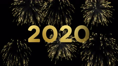 Happy New Year 2020 animation of gold fireworks explosion on black night sky background. Video greeting card with animated 20 numbers for celebration or party invitation in 4k.