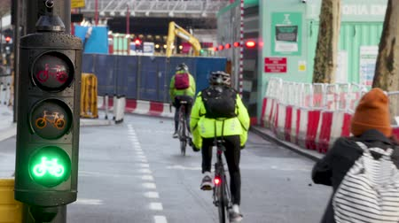andar : Cyclists ride in a busy cycle lane in London with cycle traffic lights