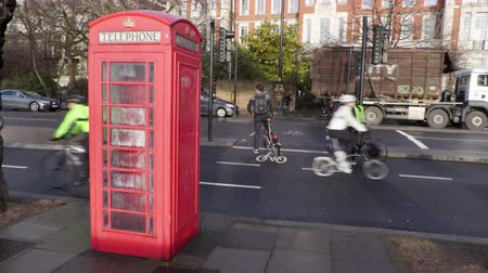 andar : Cyclists in a cycle lane go past a British phone box Vídeos