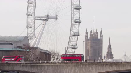 Buses go past London Eye and Big Ben