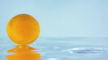 çilek : Slow Motion Footage Of An Orange Floating On Water Surface With A Blue Background