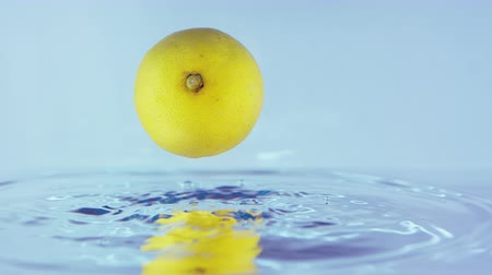 çilek : Slow Motion Footage Of A Lemon Falling On A Shiny Water Surface On A Bright Blue Background Stok Video