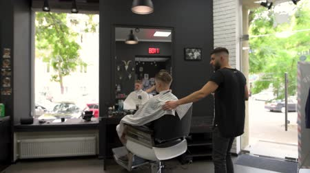 Barber combs the client during haircuts and turns in an armchair that would look at the haircut from different sides Стоковые видеозаписи