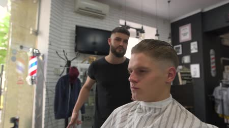 Barber takes the scissors off the table and starts cutting the client Стоковые видеозаписи