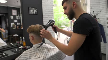 Barber dries the client with a hair dryer, and combs the comb