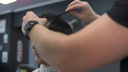 Barber combs the clients hair before cutting. front view
