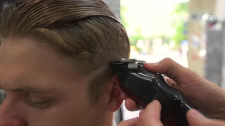 бритье : Barber shears the clients hair. side view