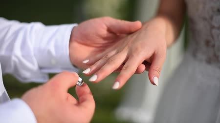 The groom wears an engagement ring on the brides finger Стоковые видеозаписи