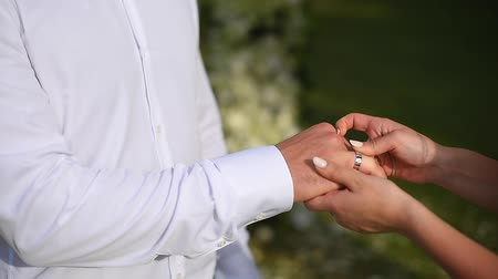 The bride dresses an engagement ring on her grooms finger.