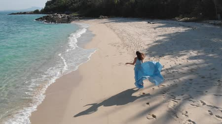 a tall girl in a blue dress runs and spins along the beach by the ocean