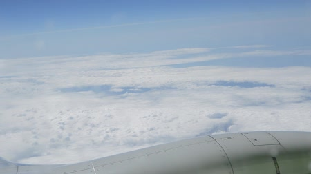 none : View through the window of the aircraft on the clouds and the wing, the flight is normal