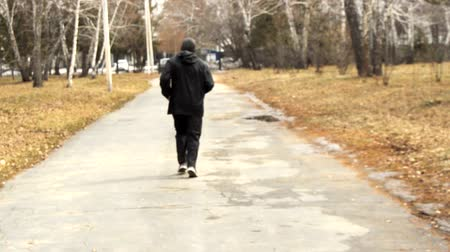 A man in black sportswear running down the park from the back. Endurance training and preparation for marathons, outdoor