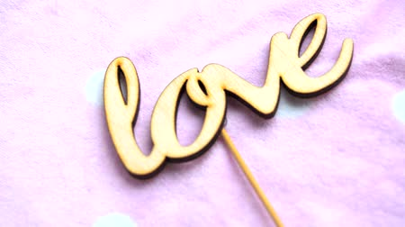 wooden type : The word LOVE made of wooden letters on a delicate pink background Stock Footage