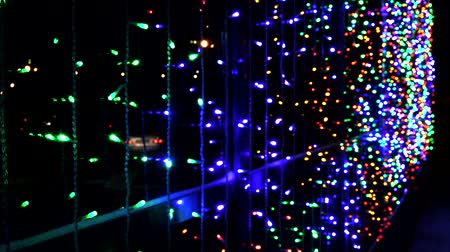 festoon : Night multicolored illumination on the office building, decoration with led garland for the holidays, reflection on the glass of moving cars