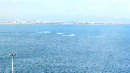 In the distance, along the coast of Spain, a sailboats and water scooters