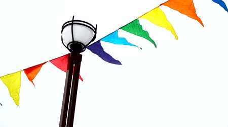 úterý : Colorful triangular flags fluttering in the wind are tied to a lamppost. Decoration for holiday, outdoor