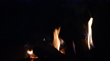 Natural flame from the fire, orange fire at night in the open space, firewood slowly burning and smoldering, rural life