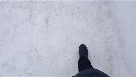Top view, a selfie of a man walking carefully through the snow on a slippery road. Careful driving in ice in winter. First person view 4K video Stock mozgókép