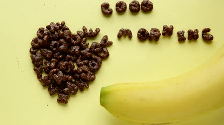 banan : On a yellow background, a heart sign made of chocolate corn flakes, written in the letters Good morning, a banana in the shape of a smile, the concept of a good start to the day. Wideo