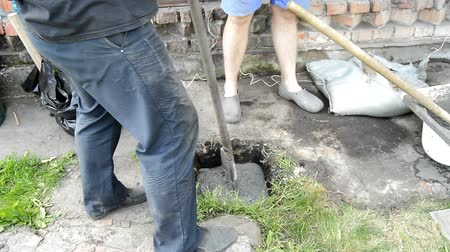Two workers fill a hole in the ground with mortar or cement for concreting a pile on their land plot, a summer Sunny day