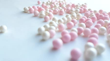 katalog : Small mother-of-pearl white and pink balls or make-up powder beads roll on a white background, minimal idea concept, 4k video