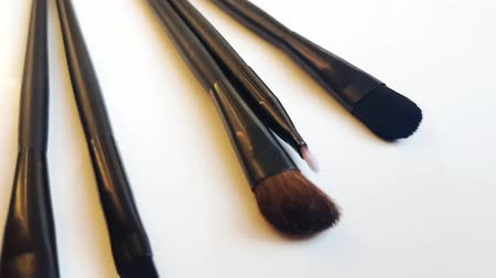Set of black makeup brushes and cosmetics on a white background, beauty concept. Slow motion, top view, 4k video, clean unused brushes. Stock mozgókép