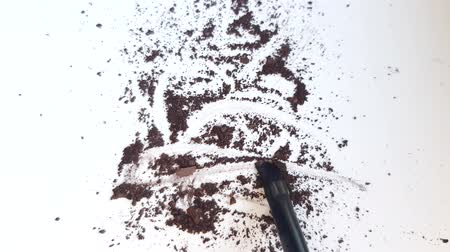 Scattered brown eye shadow on a white background, movement of the makeup brush on the texture of the powder.