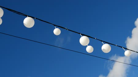 White garland balloons oscillate in the wind against blue sky and clouds, peaceful landscape Stockvideo